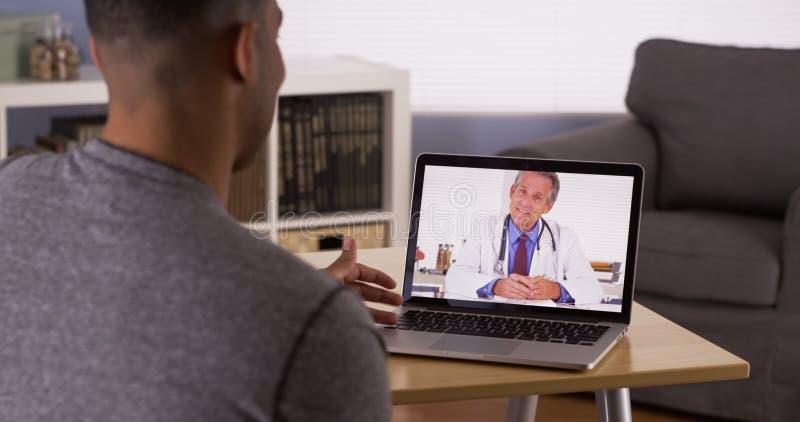 Paziente nero che discute i problemi sanitari con medico online fotografie stock libere da diritti