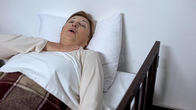 Paziente pensionato della donna che si trova nell'attacco di asma ritenente del letto di ammalato e che chiede l'aiuto fotografie stock