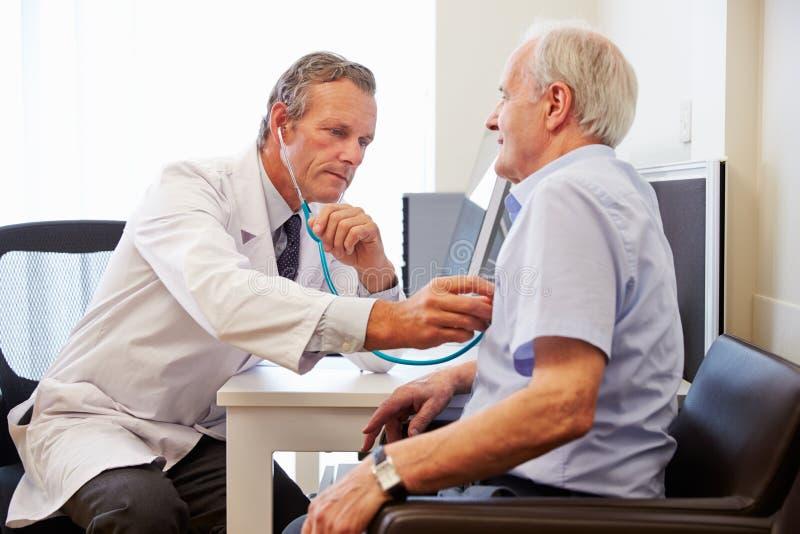 Paziente senior che ha esame medico con il dottore In Office immagine stock libera da diritti