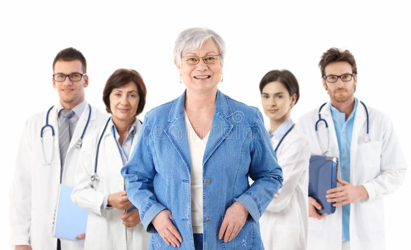 Paziente senior davanti al gruppo di medici fotografie stock libere da diritti