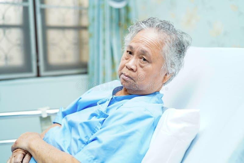 Paziente senior o anziano asiatico della donna della signora anziana che si siede sul letto nel reparto di ospedale di cura con s immagini stock