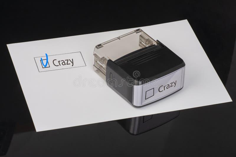 Pazzo - casella di controllo con un incrocio su Libro Bianco con la matrice di gomma della maniglia Concetto della lista di contr fotografia stock libera da diritti
