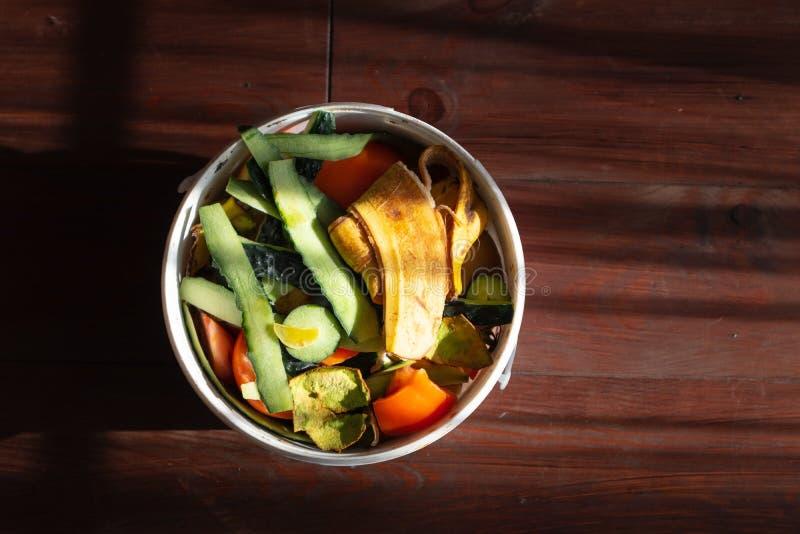 Pbucket bianco di ortaggi e di bucce di frutta contro pavimenti di legno marrone scuro fotografie stock