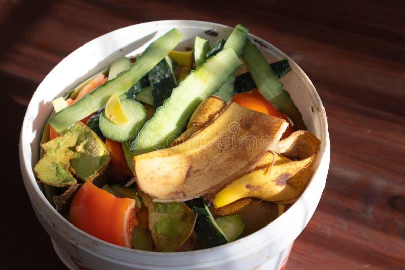 Pbucket bianco di ortaggi e di bucce di frutta contro pavimenti di legno marrone scuro immagini stock