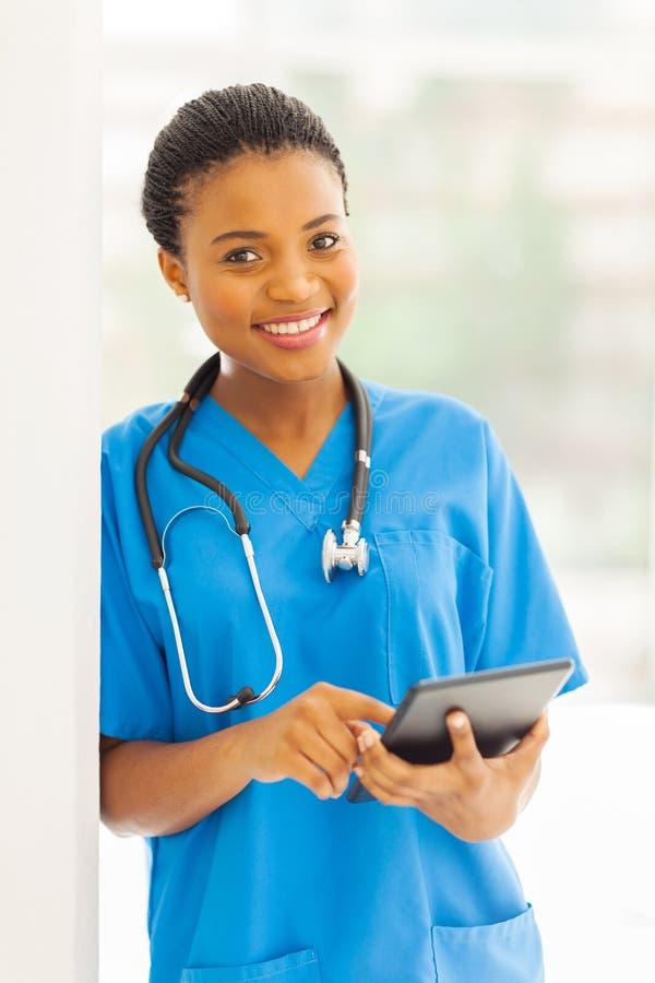 PC africana de la tableta de la enfermera foto de archivo