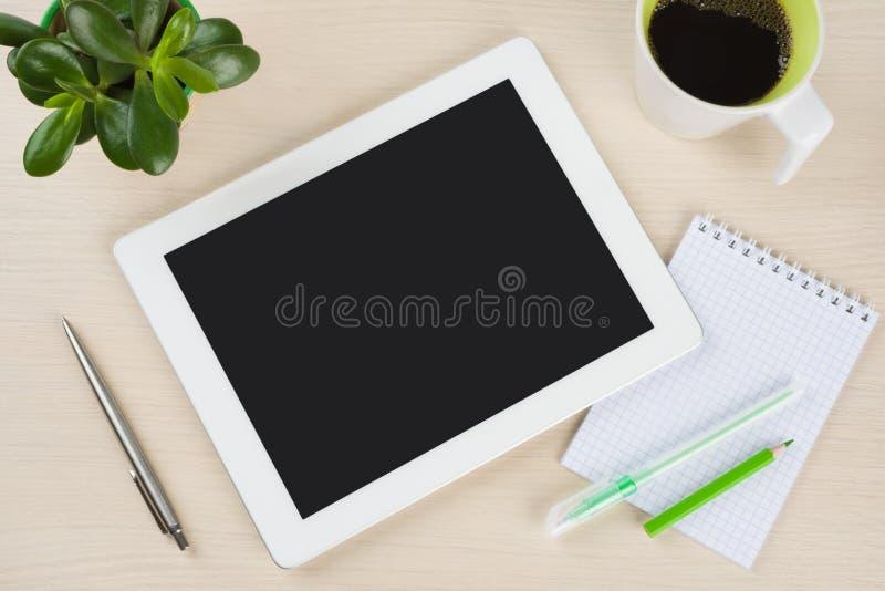 PC branco da tabuleta com o copo das notas, da pena e de café na mesa fotos de stock
