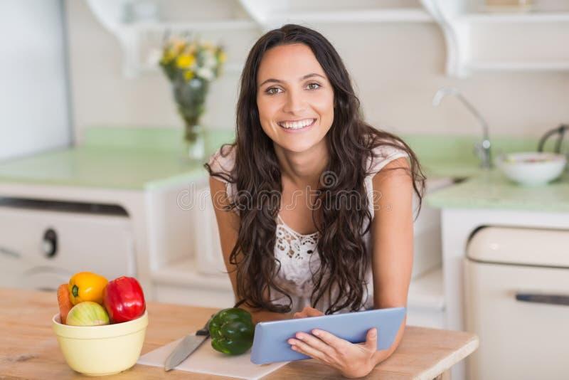 PC da tabuleta e salada de utilização morenos bonitos da preparação imagens de stock