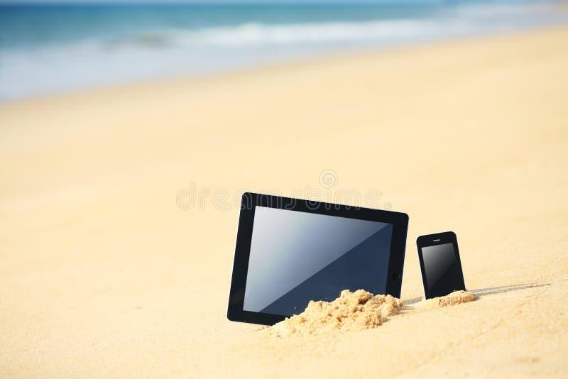 PC da tabuleta. e smartphone na praia imagem de stock royalty free