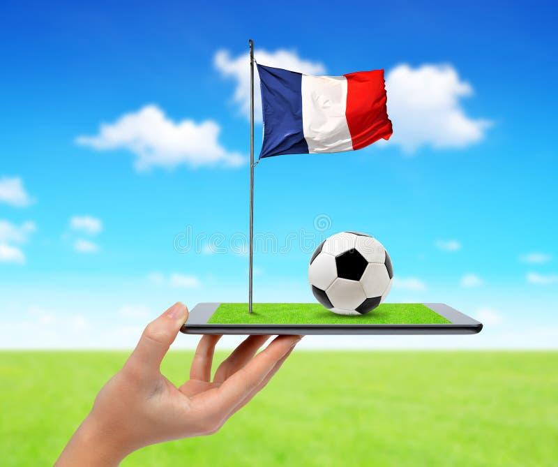 PC de comprimé de Digital avec du ballon de football et le drapeau de Français images stock
