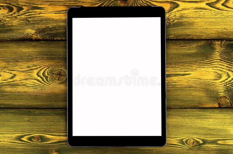 PC de la tableta con mofa de la pantalla en blanco para arriba en fondo de madera amarillo de la tabla Tableta en la tabla de mad fotografía de archivo libre de regalías
