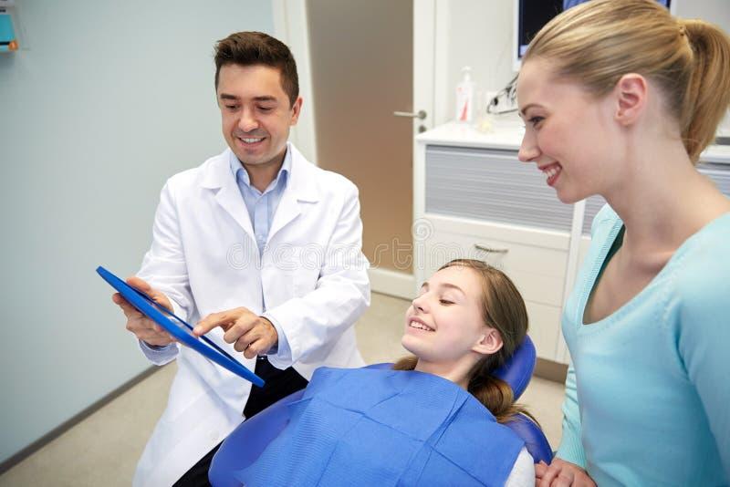 PC de la tableta de la demostración del dentista a la muchacha y a su madre imagen de archivo