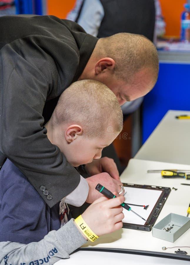 PC de la tableta de la reparaci?n del muchacho en ECO 2019 en Kiev, Ucrania imagen de archivo libre de regalías