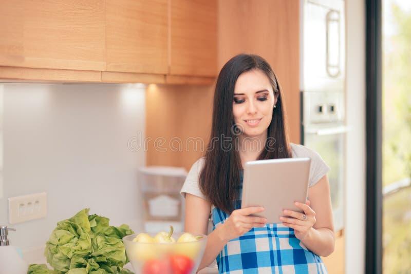 PC de Tablette de participation de femme recherchant des recettes en ligne image libre de droits