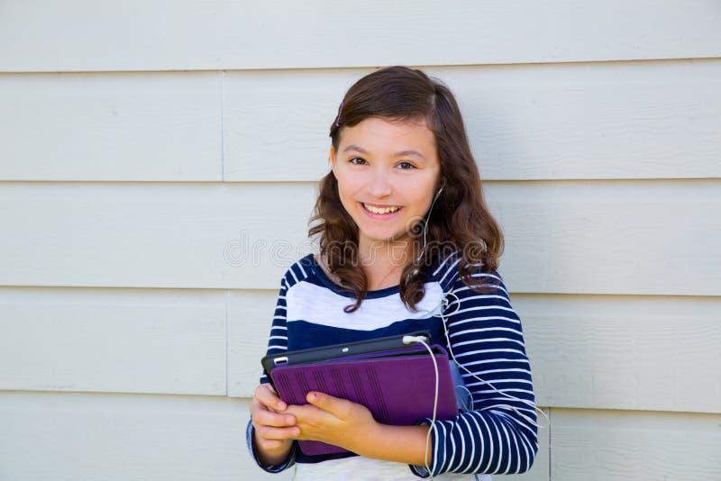 Pc e earings felici della compressa della tenuta della ragazza teenager immagini stock