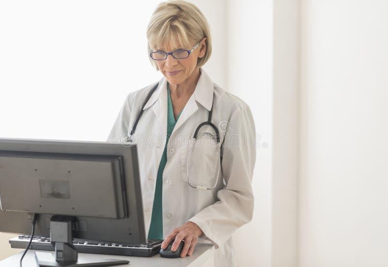 PC fêmea do doutor Using Desktop na mesa foto de stock