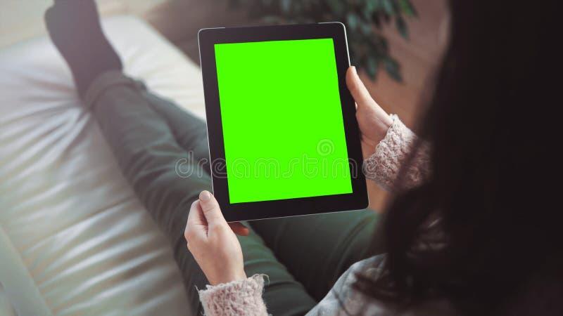 PC för kvinnabruksminnestavla som sitter på soffan fotografering för bildbyråer