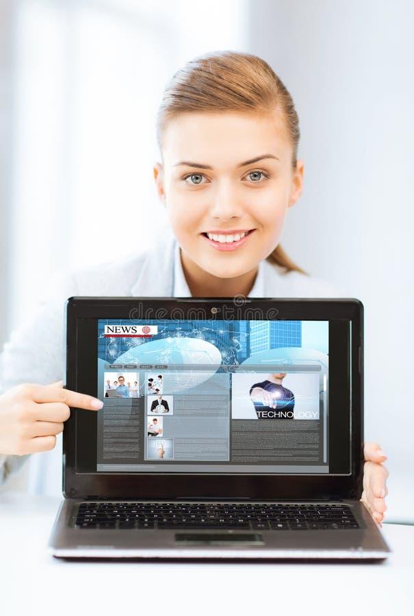 PC för kvinnavisningbärbar dator med nyheterna fotografering för bildbyråer