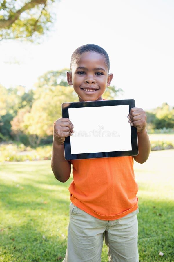 PC feliz de la tableta de la tenencia del niño mientras que se coloca fotos de archivo libres de regalías