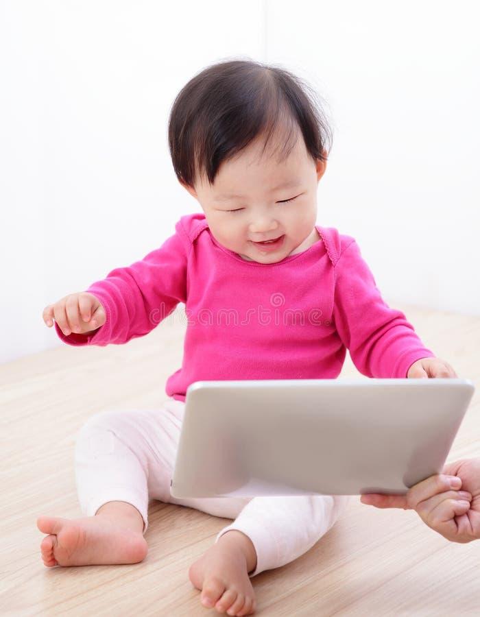 PC feliz de la tablilla del reloj del bebé de la muchacha imágenes de archivo libres de regalías