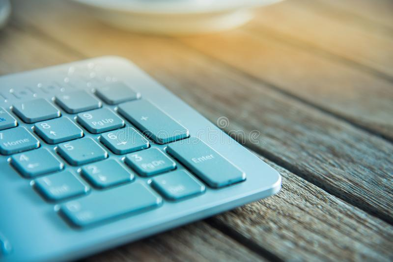 PC keyboard and cup of coffee on old weathering wooden table.  royalty free stock images