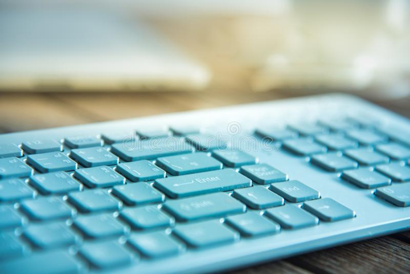 PC keyboard and cup of coffee on old weathering wooden table. Close up on keyboard stock images