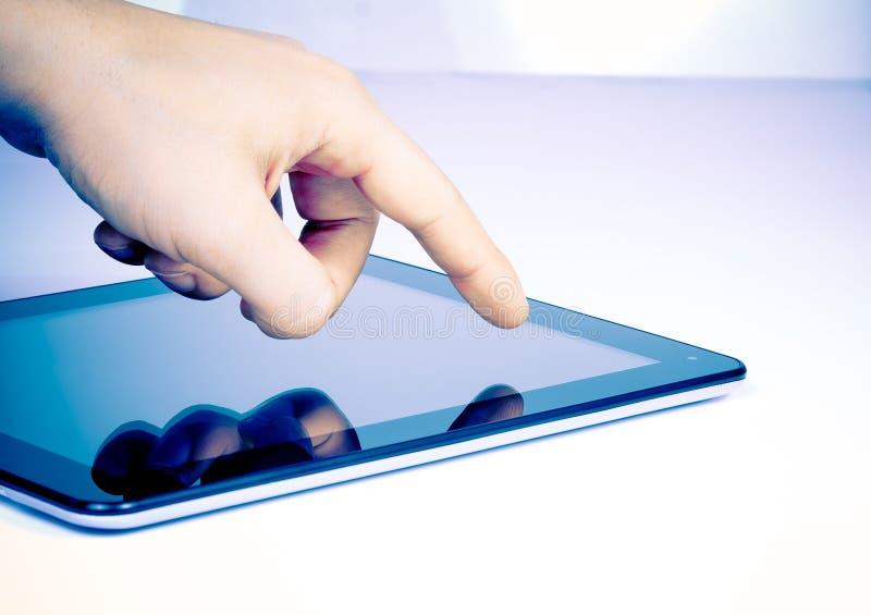 PC masculin de tablette tactile de main sur la table photos stock