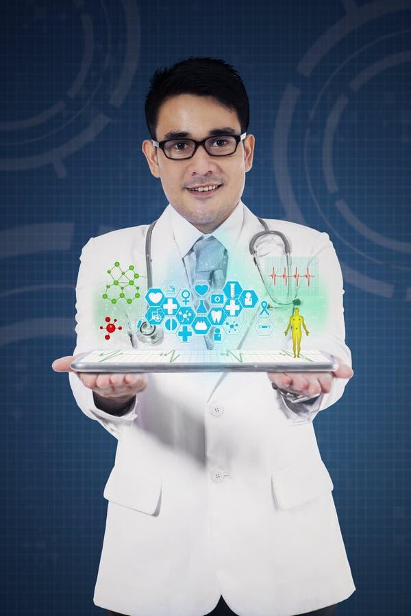PC masculina de la tableta de la tenencia del doctor imagen de archivo