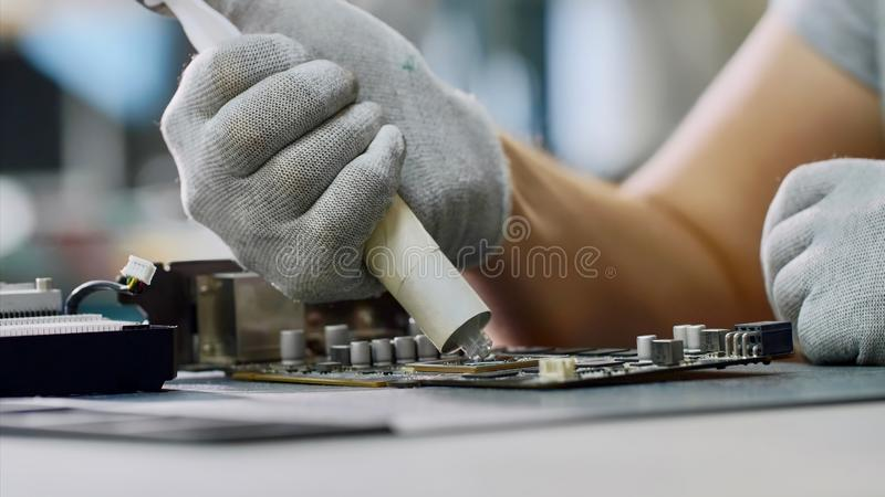 Repairman putting thermal paste on processor of graphics chipset at workshop. PC repair and maintenance in service center. Repairman puts thermal paste on royalty free stock image