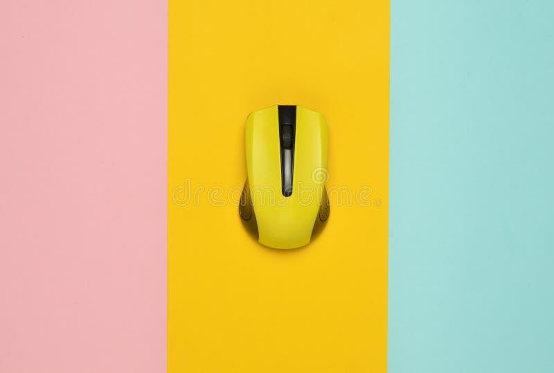 PC sem fio em um fundo de papel multi-colorido, minimalismo do rato, vista superior fotos de stock