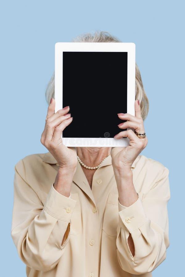 PC senior della compressa della tenuta della donna davanti al suo fronte contro fondo blu immagini stock