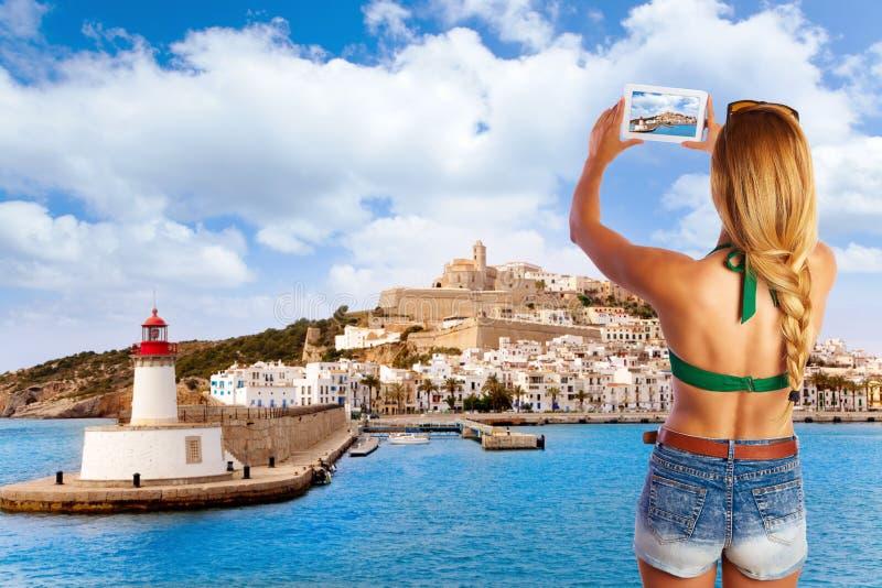 Pc turistico biondo della compressa della foto nell'orizzonte di Ibiza fotografie stock