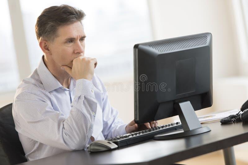 PC van zakenmanworking on desktop in Bureau stock foto's