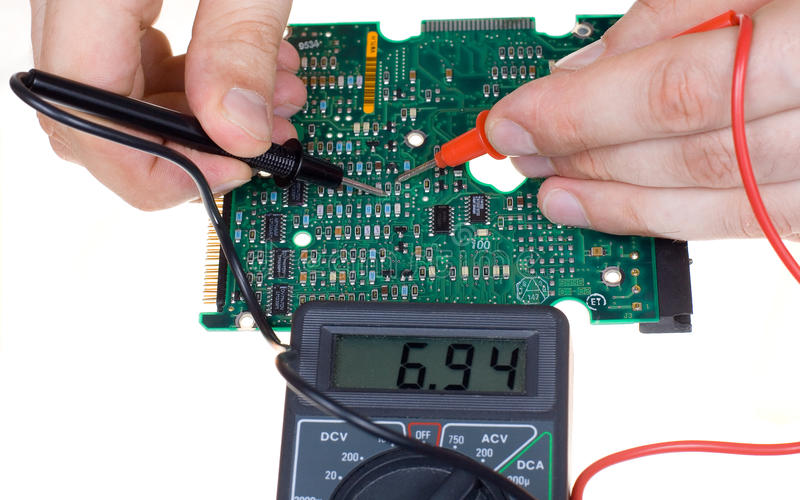 PCB and multimeter. PCB diagnostics and measurement by means of a multimeter stock images