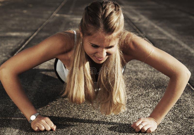 Pcha podnosi lub prasa podnosi ćwiczenie młodą kobietą Dziewczyna pracująca out zdjęcie stock