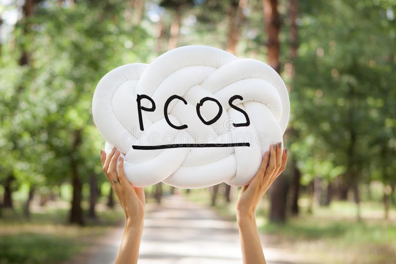 PCOS - Polycystic ovary syndrome, woman sickness lettering on white background in womans hands. PCOS - Polycystic ovary syndrome, woman sickness lettering on stock image