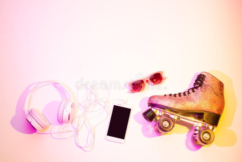 Pcteres de ruedas, smartphone, auriculares y gafas de sol fotografía de archivo