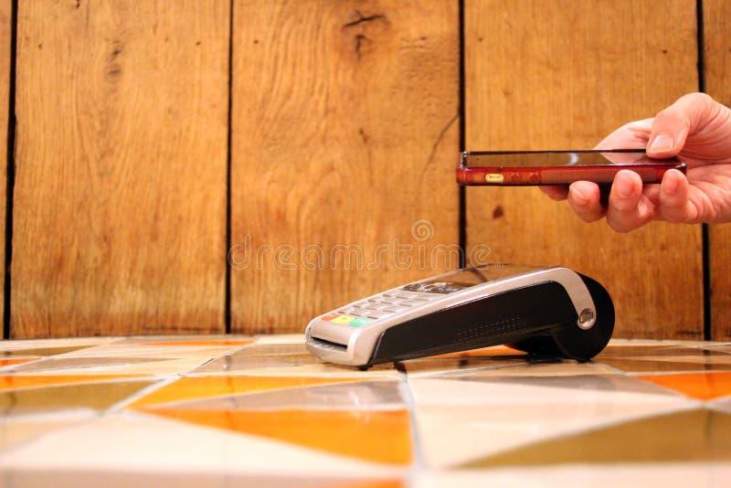 pdq senza contatto del telefono di pagamento con la carta di credito della tenuta della mano da pagare immagini stock
