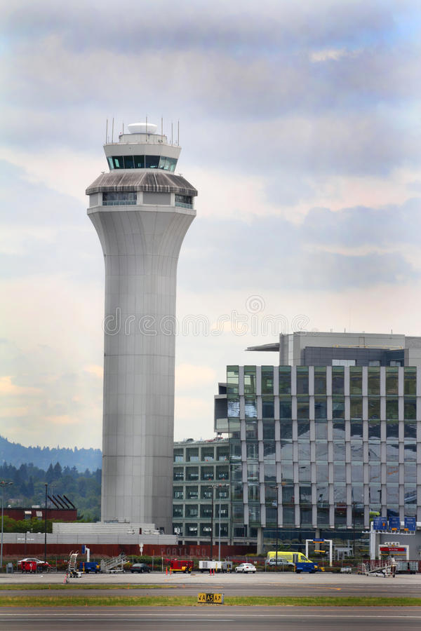 PDX Traffic Control Tower. The air traffic control tower sits beside a large parking garage, and behind the plane and baggage service area. Turbulent skies royalty free stock photo