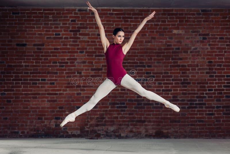Pełen wdzięku balerina w czerwonym bodysuit doskakiwaniu w powietrzu zdjęcie stock