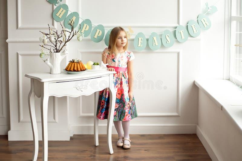 Pełna długość uśmiechać się dziewczyny w kolorowej sukni pozuje w dekorującym pokoju dla wakacyjnej wielkanocy troszkę czekać na zdjęcia royalty free