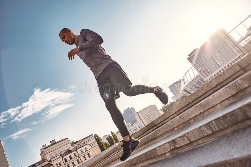 Pełny energetyczny Pełny długość portret sportowy afrykański mężczyzny bieg na schodkach z bardzo szybką prędkością na pogodnym r obrazy stock