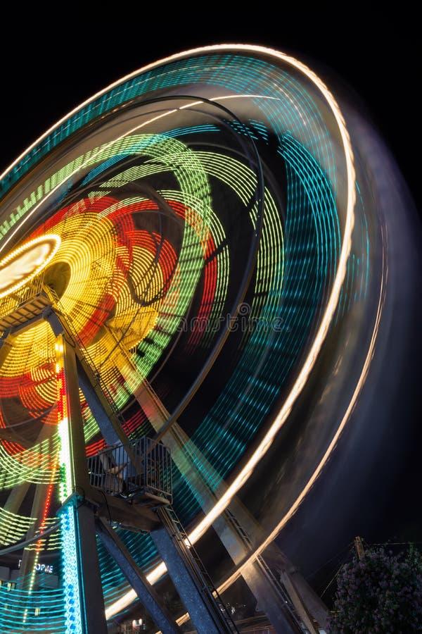 Peça borrada de uma roda de Ferris na noite com cores em mudança Monte o giro, criando raias claras na noite imagens de stock royalty free