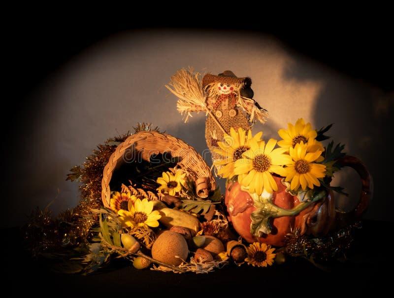 Peça central da cornucópia da ação de graças com o jarro da abóbora da porcelana, o espantalho, os girassóis e as folhas do carva fotos de stock royalty free