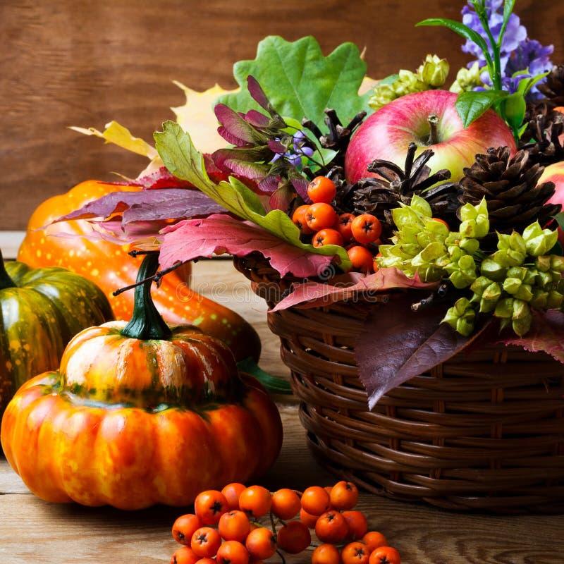 Peça central da tabela da ação de graças com maçãs e folhas no vime imagem de stock