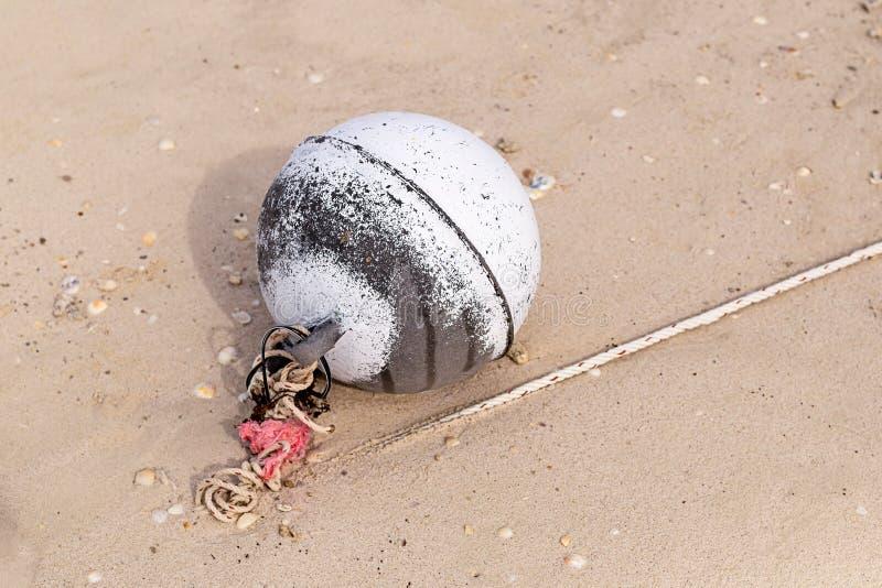 A peça da boia das artes de pesca jogada na costa arenosa do círculo espumoso velho do oceano resistiu ao projeto imagens de stock royalty free