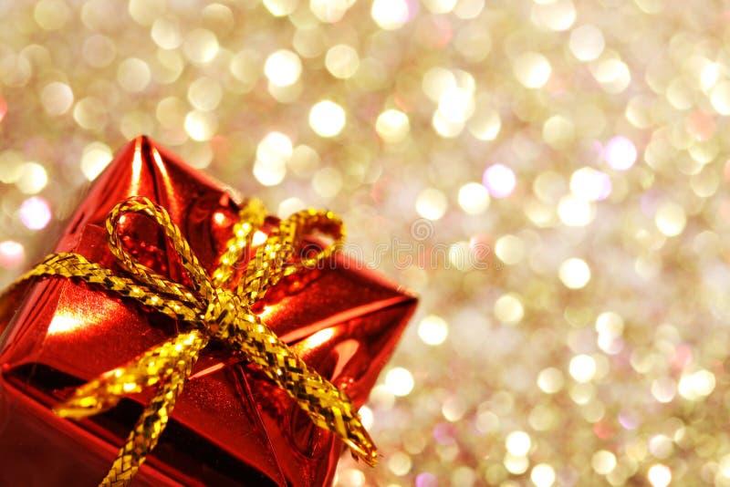 Peça da caixa de presente vermelha do Natal com curva amarela no fundo da prata e do ouro do brilho fotografia de stock