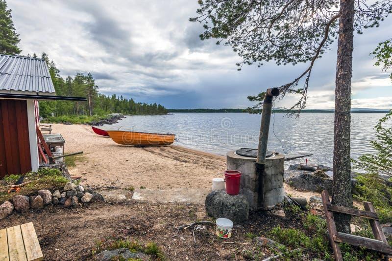 Peça da casa de madeira e dos utensílios domésticos na beira do lago Sandsjon em Lapland sueco Os barcos de madeira do fogão e de imagens de stock