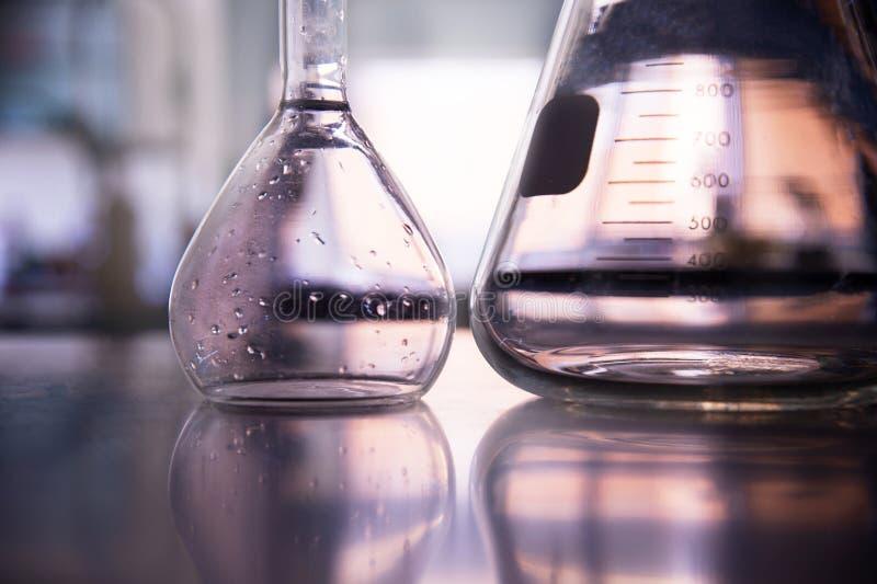 Peça da garrafa de vidro volumétrico e cônica no fundo do laboratório de ciência da educação fotos de stock