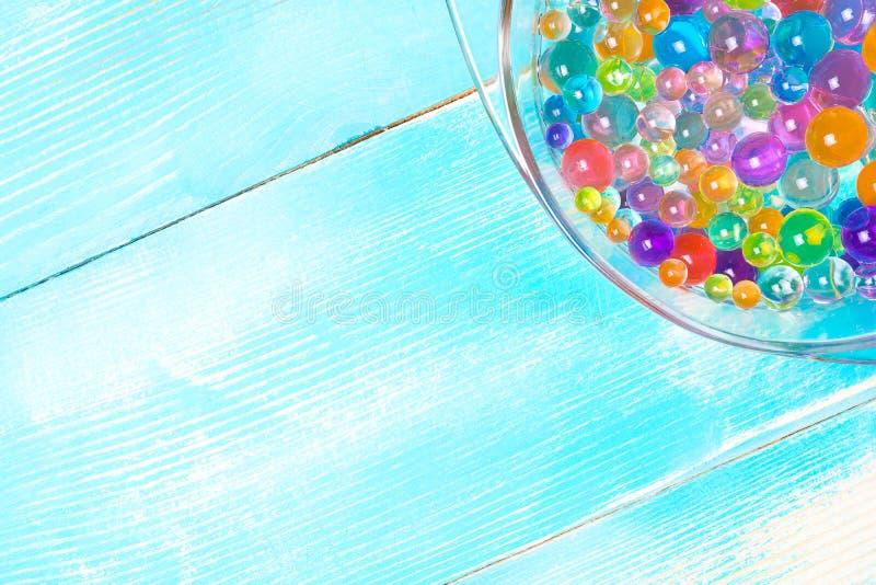 Peça da placa com as bolas multi-coloridas do hydrogel em um de madeira fotografia de stock