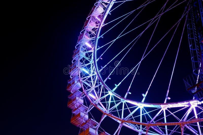 Peça da roda de ferris com iluminação roxa na noite fotografia de stock royalty free